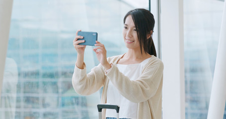Woman taking photo on cellphone in airport