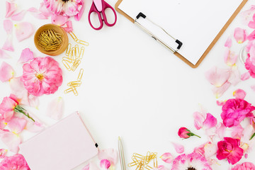 Workspace with clipboard, pastel roses and accessories on white background. Flat lay, top view. Copy space