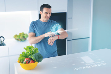 Happy man. Cheerful young man standing in a modern kitchen and smiling while looking at the projection on his smart watch