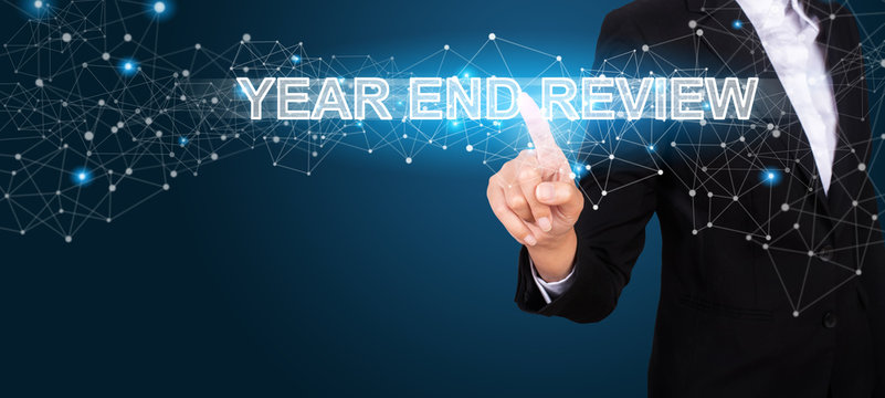 Year End Review concept with Hand of business pressing a button Year End Review