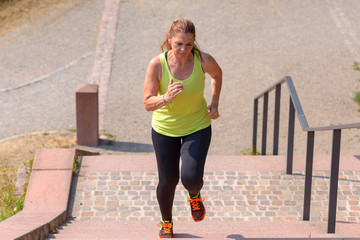 Woman running while climbing stairs during workout