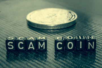 Words Scam coin made of black cubes on grey.