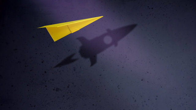 Start-up Company and Motivation in Business Concept. Paper Planes Flying with Shadow of Rocket by the Wall