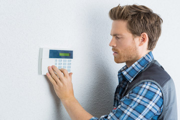 Man entering code on alarm keypad