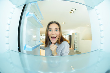 Woman looking excitedly into empty fridge