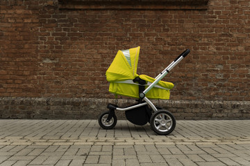 a yellow baby stroller stands on the road beside the wall