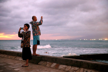 People take pictures of Waikiki Bay as Tropical Storm Lane approaches Honolulu