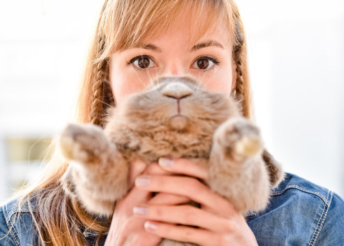 Young woman hugs big cute rabbit friend pet in her hands. Funny portrait with bunny