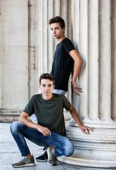 Männliche Zwillinge posen in antiker Kulisse
