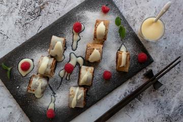 banan pancake sushi dessert with dip and chocolate syrup