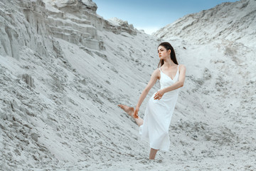 Fashionable nice and sensuality brunette woman in white dress dancing on the desert at blue sky