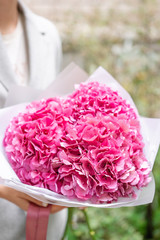 pink hydrangea. Young girl holding a flower arrangement. Beautiful summer bouquet. The concept of a flower shop. Content for the catalog