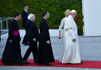 Pope Francis walks with Ireland's President Michael Higgins and his wife Sabina Coyne during his visit in Dublin