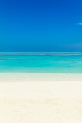 Blue sea water surface, clear sky and sandy seashore