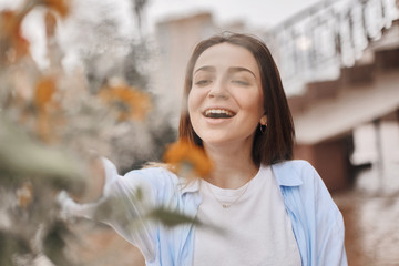 a beautiful woman is given a bouquet of flowers. a brunette dressed in a blue shirt and a white T-shirt with takes a bouquet of field flowers. lady is happy and with amazed face.