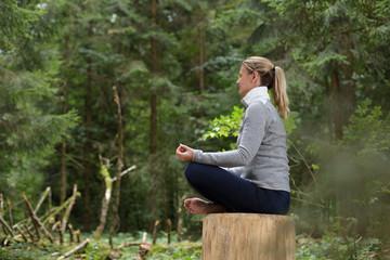 Frau beim Entspannen Meditieren im Wald