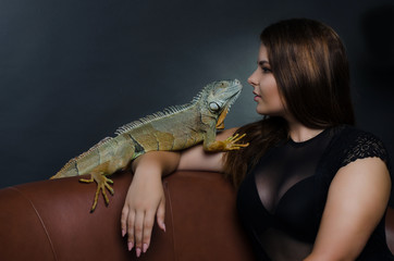 beautiful big tits girl and green iguana in the studio
