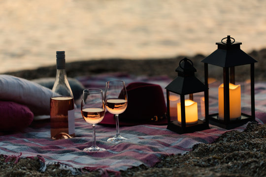 Summer sea sunset. Romantic picnic on the beach. Bottle of wine, glasses, candles, plaid and pillows.