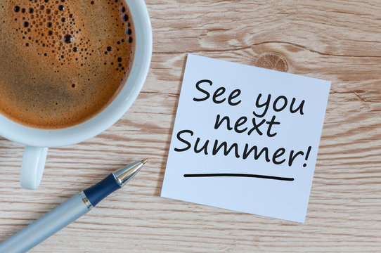 See you next Summer written on a note at the table with morning coffee cup and empty space for text