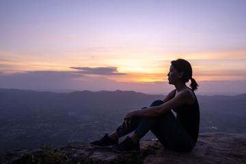 silhouette woman sitting on mountain