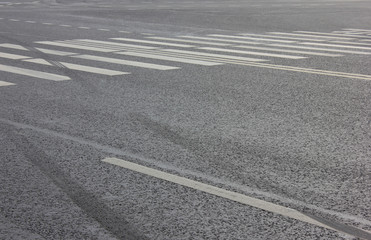 Crosswalk on City Street with Parallel Painted White Zebra Lines and Empty Asphalt Road Background. Pedestrian Cross Walk View with Traces from Wheel Tires at Crossing Point on City Street