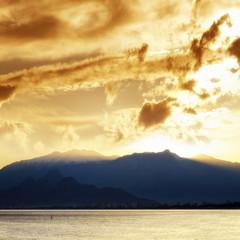 seascape image of high mountains  over orange sunset sky