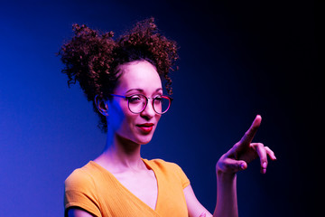 Smart girl with glasses and  finger raised about to press something , isolated on dark blue background