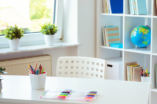 Interior of child room with white table and colorful pencils on him and shelf with books