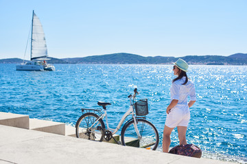 Back view of slim tourist woman in white clothing and sunglasses resting at bicycle and backpack on paved stone sidewalk stairs on clear blue sea water, sailing cruse yacht and mountains background.