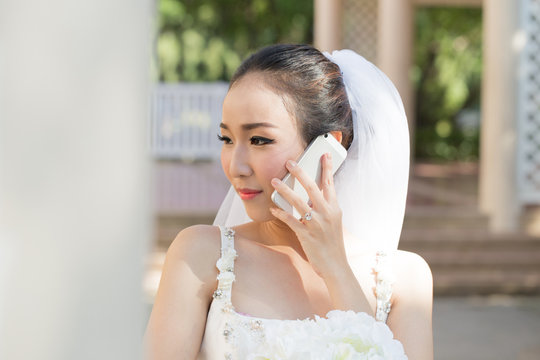 Beautiful Attractive Asian bride talking with her friend in smart phone in wedding day feeling so proud and happiness