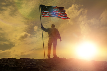 Silhouette of man holding US flag American on the mountain. The concept of Independence Day. a successful silhouette winner, a man waving an American flag on top of a mountain peak