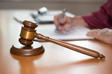 judge writing note with legal law gavel on desk. lawyer attorney justice at office
