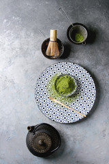 Ingredients for making matcha drink. Green tea matcha powder in ceramic bowl, traditional bamboo spoon and whisk on decorative plate, black iron teapot over grey texture background. Flat lay, space