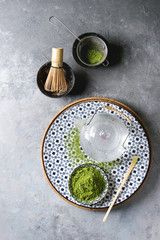 Ingredients for making matcha drink. Green tea matcha powder in ceramic bowl, traditional bamboo spoon and whisk on decorative plate, glass teapot over grey texture background. Flat lay, space