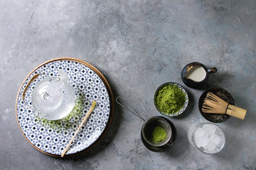 Ingredients for making matcha ice drink. Green tea matcha powder in ceramic bowl, traditional bamboo spoon, whisk on plate, glass teapot, ice cubes over grey texture background. Flat lay, space