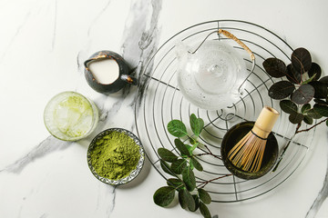Ingredients for making matcha ice drink. Green tea matcha powder in ceramic bowl, traditional bamboo spoon, whisk on cooling rack, glass teapot, ice cubes over white marble background. Flat lay, space