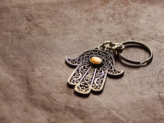 A key ring in the form of Fatima Hand on a brown leather background. Ancient symbol and traditional modern tourist souvenir of Tunisia