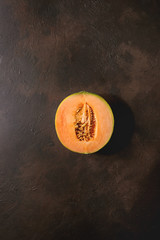 Half of ripe organic Cantaloupe melon with seeds over dark brown texture background. Flat lay, space