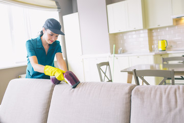 A picture of girl cleaning edge of sofa. She uses small vacuum cleaner. Woman is professional. She does work perfectly.