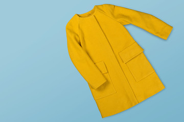 yellow woolen female coat on a blue background, concept of shopping and fashion