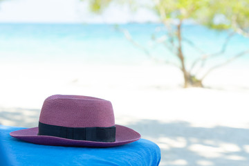 Purple women hat on beach chair on beach background with copy space