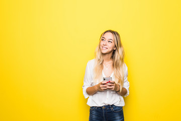 Portrait of a young woman using mobile phone isolated over yellow background Wall mural