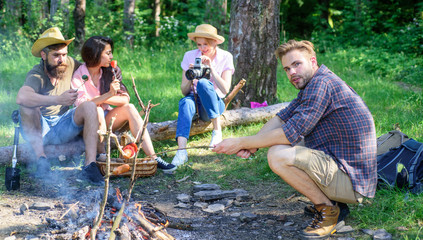 Hike picnic ideas. Hikers sit near campfire relaxing while wait roasting food. Hikers organized quick picnic to eat and relax. Hikers spend leisure in forest nature background. Youth hiking vacation