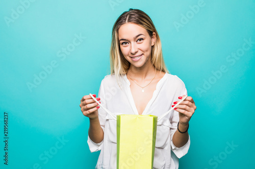 88155065 Portrait of a curious young woman holding shopping bags and looking away  isolated over green background