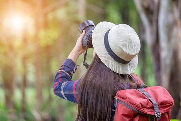 Young traveler woman with backpack and hat standing with camera travel photo of photographer making pictures in hipster style