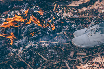 A pair of camp shoes is dried near a fire in the forest
