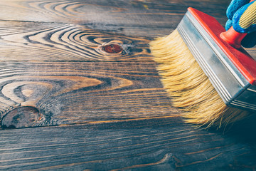 Obraz Hand brush covers with oil old wooden floor - repair and restoration of the floor - fototapety do salonu