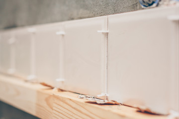 The tiler puts the first row of tiles on the kitchen wall on a wooden bar