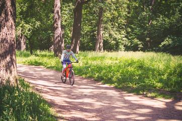 Cyclist in helmet on orange bike riding in park