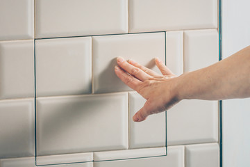The girl neatly closes the technical hatch on the wall of tiles